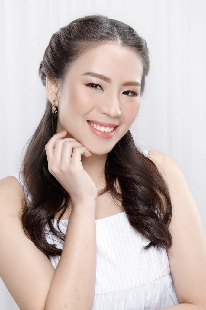 Asian woman with half up rope braid hairstyle wearing a white sleeveless dress and smiling