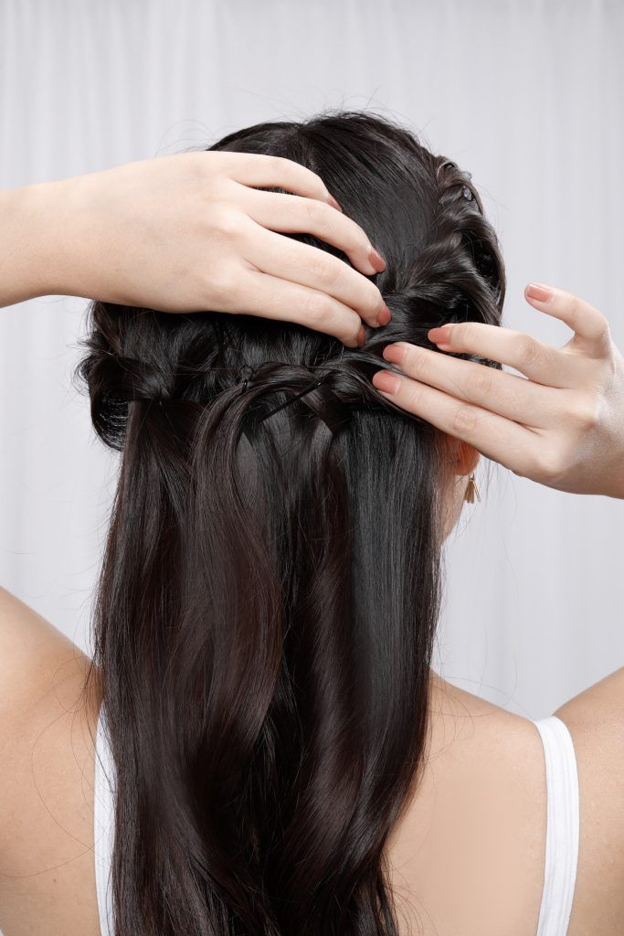 Back shot of an Asian woman pinning her half up rope braid