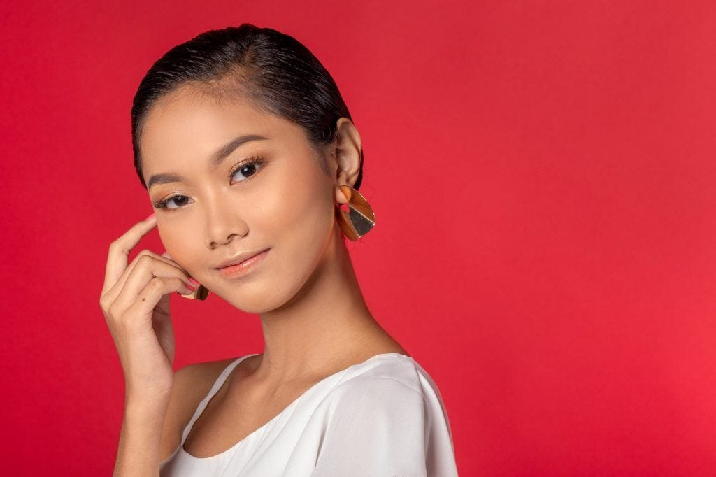 Asian woman with a short haircut for oval faces standing against a red background