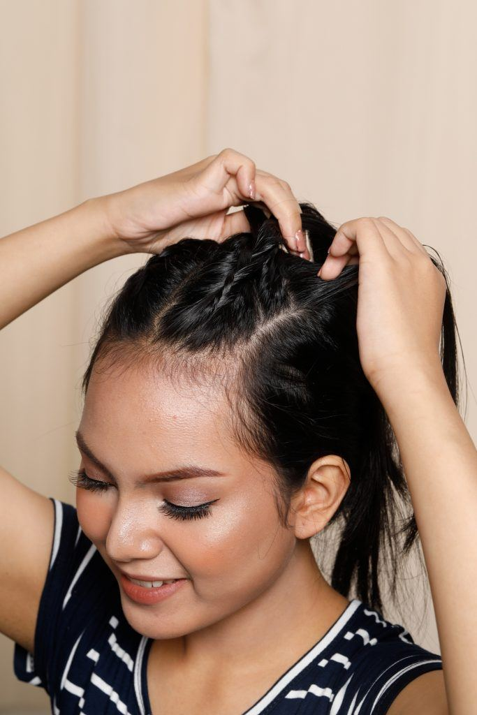 Asian woman braiding one section of her short hair