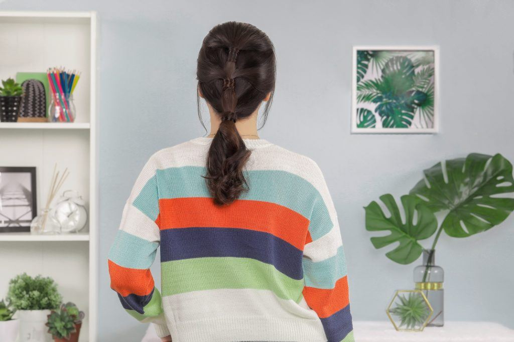 Back shot of an Asian woman with three-ponytail hairstyle wearing a colorful jacket