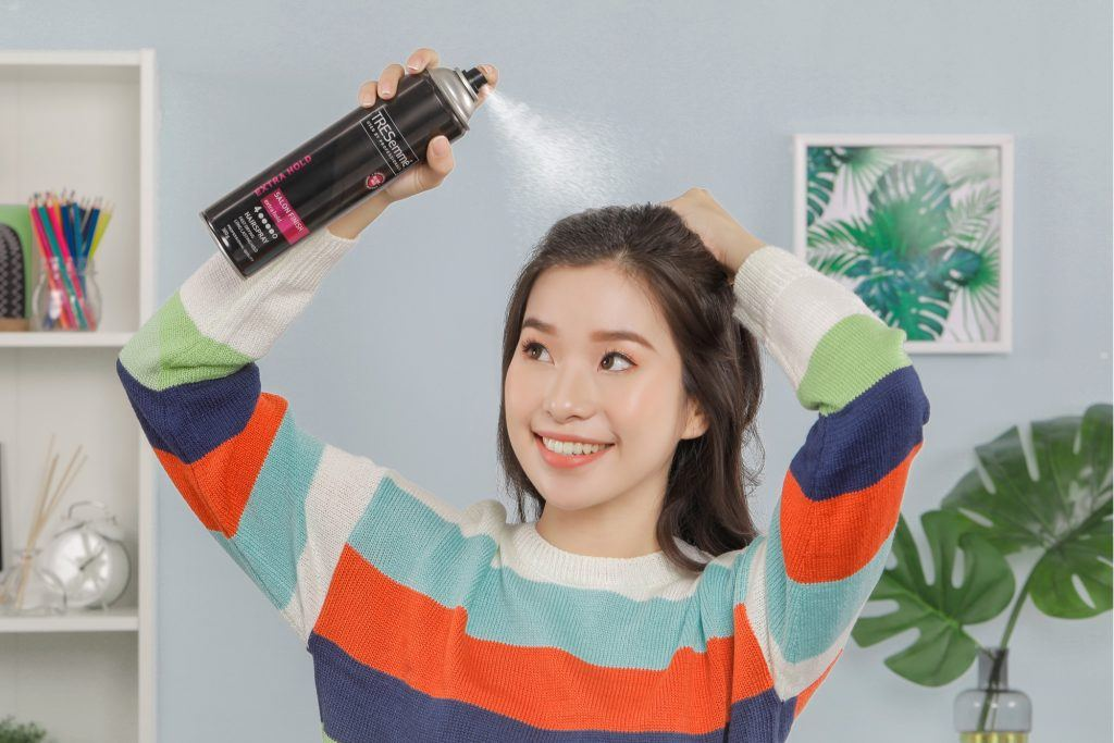 Asian woman spritzing hairspray on her simple hairstyle