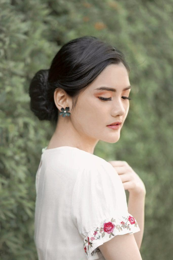Asian woman wearing a white dress with hair in a twisted updo standing against a leafy wall