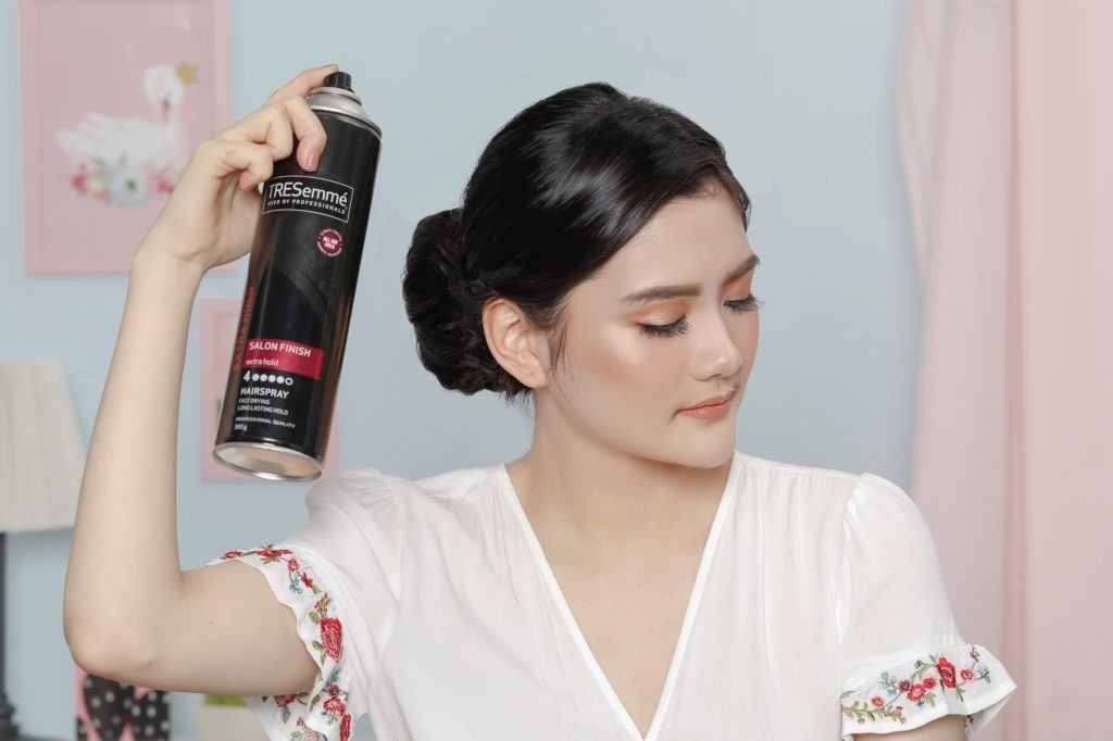 Asian woman spraying hairspray on her twisted updo