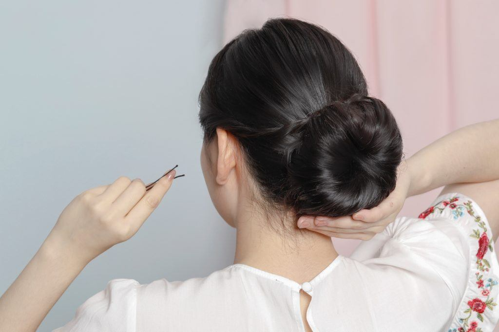 Back shot of an Asian woman creating a twisted updo