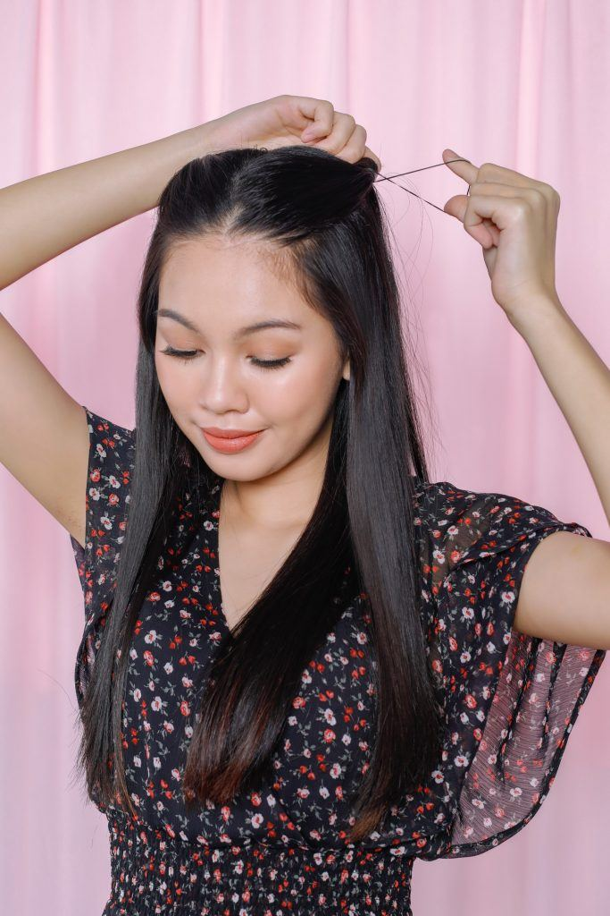 girl is seen tying her hair for one of the easy braided hairstyles