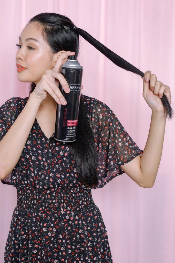 easy braided hairstyles: girl is spraying some hairspray on her hair