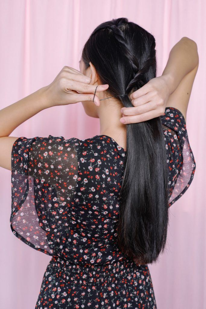 girl is tying her hair with an elastic