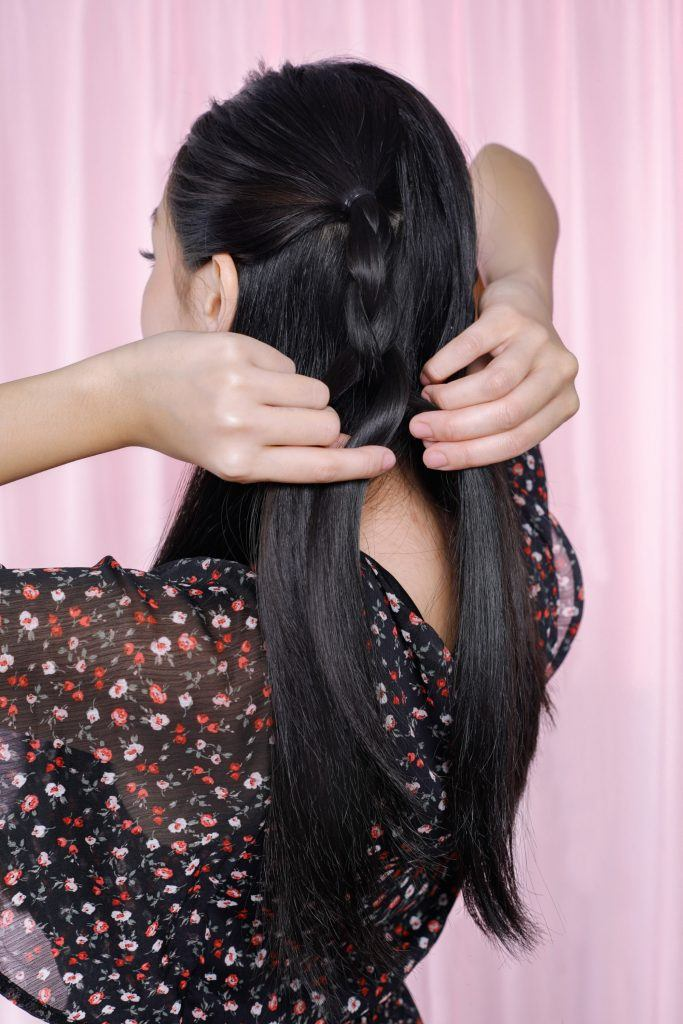 girl is showing how to braid her hair