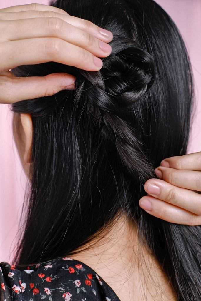 easy braided hairstyles: girl is showing how to twist the braided hair