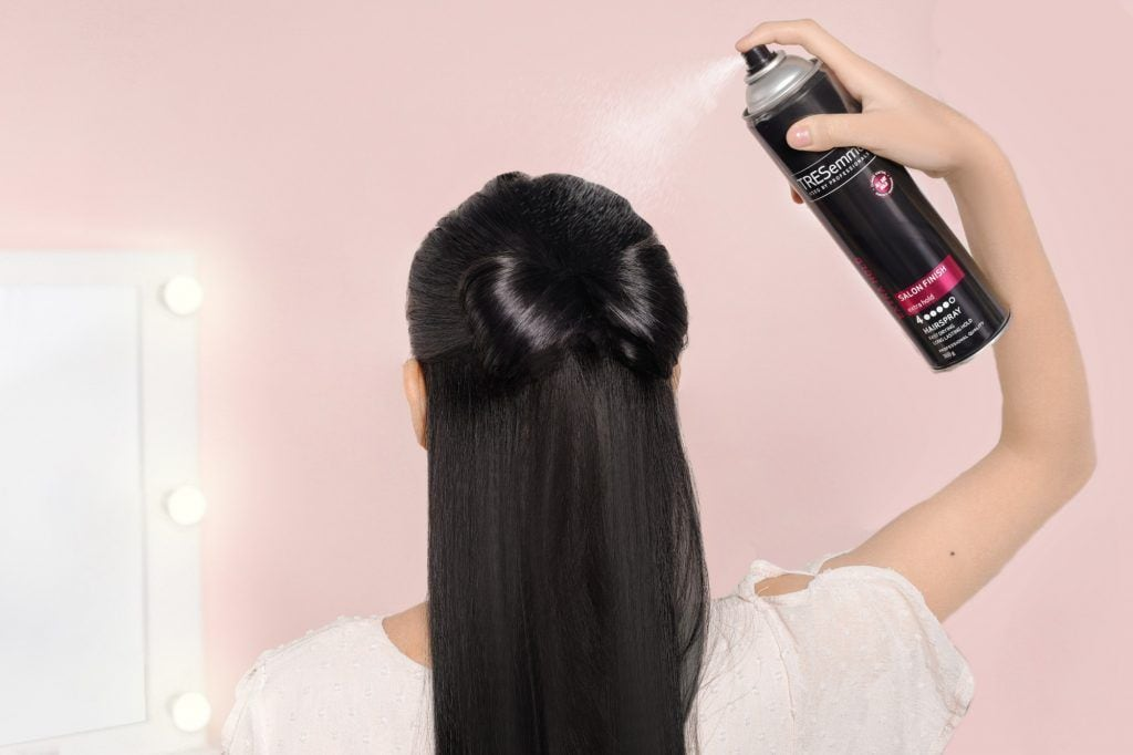 Asian woman spraying hairspray on her half up bow updo