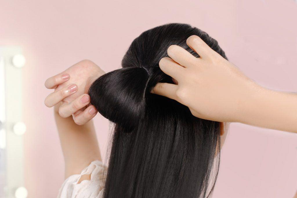 Asian woman tying a half updo