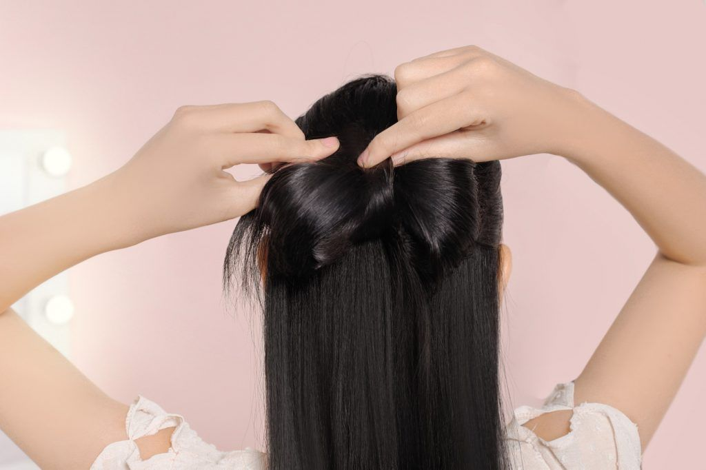Easy hairstyles for long hair: girl is making a ribbon