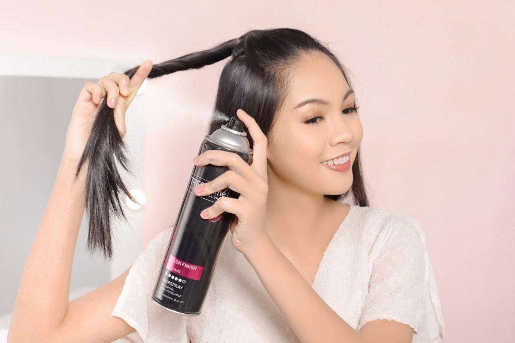Asian woman twisting her hair and spraying hairspray