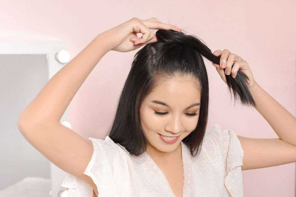 easy hairstyles for long hair: girl is wrapping her twisted hair around the base