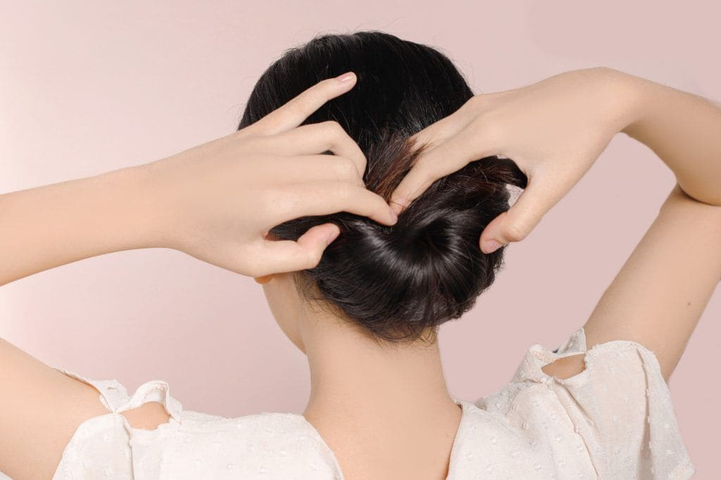 girl is showing how to insert her hair for the inverted bun