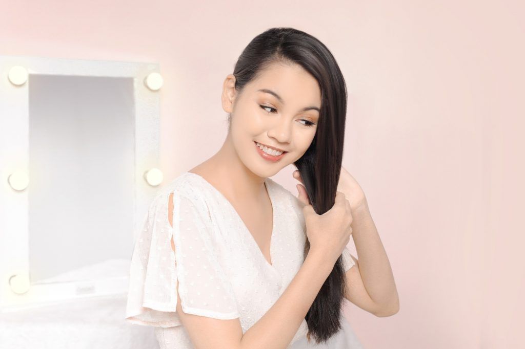 Asian woman holding her long black tresses