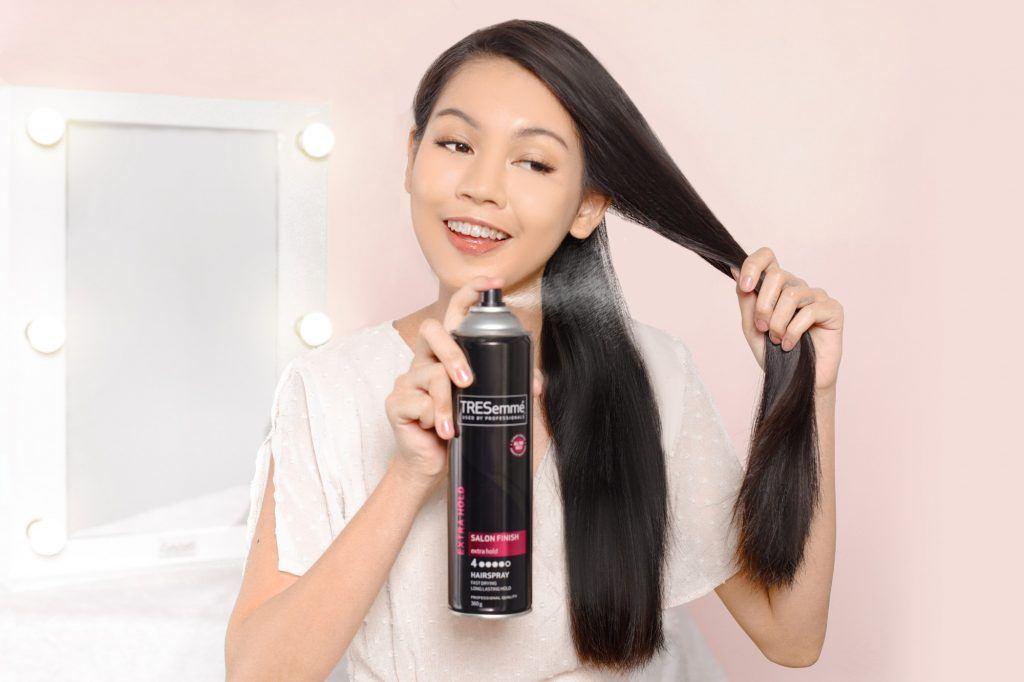 girl is spraying hairspray on her hair