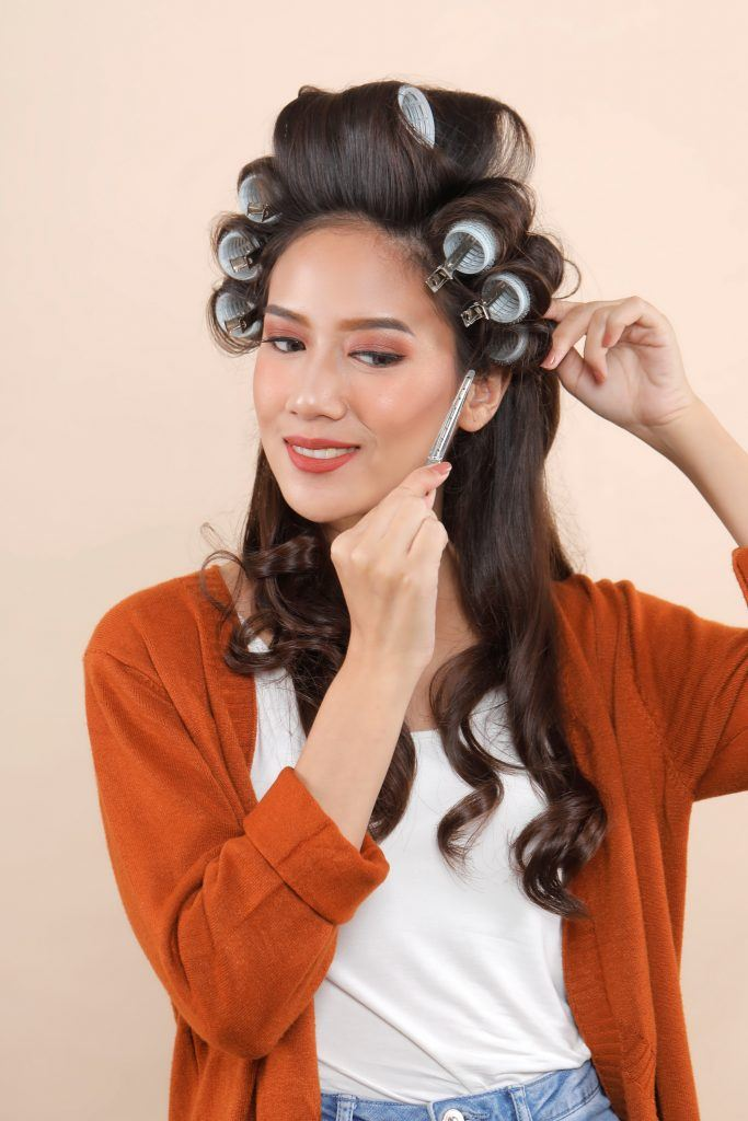 Asian woman removing hair rollers from her long hair
