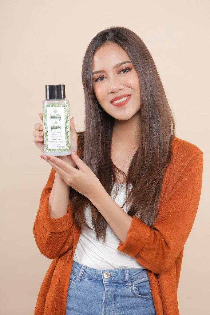 Asian woman with long hair holding a conditioner bottle