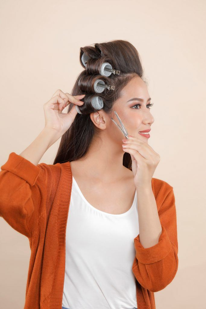 Asian woman putting hair rollers on her long hair