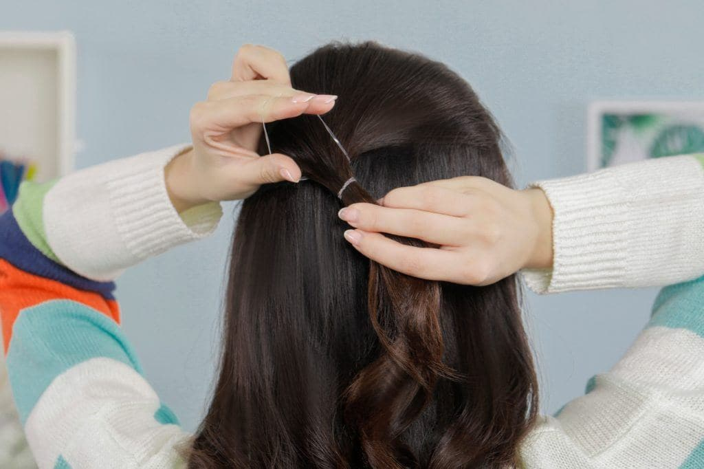girl facing her back is tying her hair with an elastic for a simple hairstyle