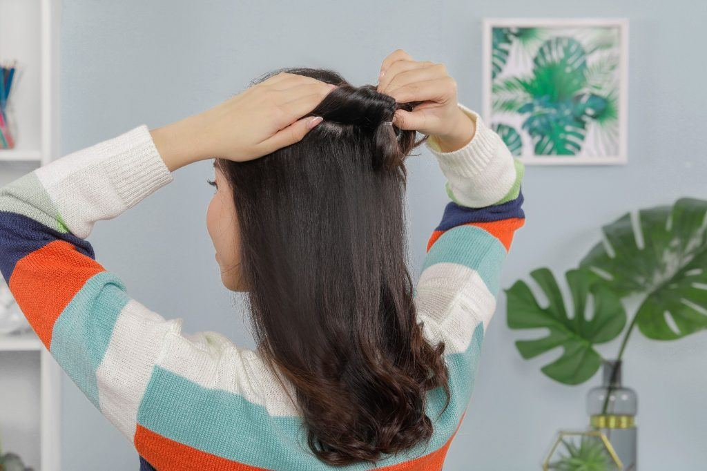 girl is holding the back of her hair to create a gap