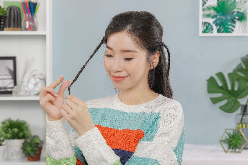 Asian girl is braiding her hair to create a simple hairstyle