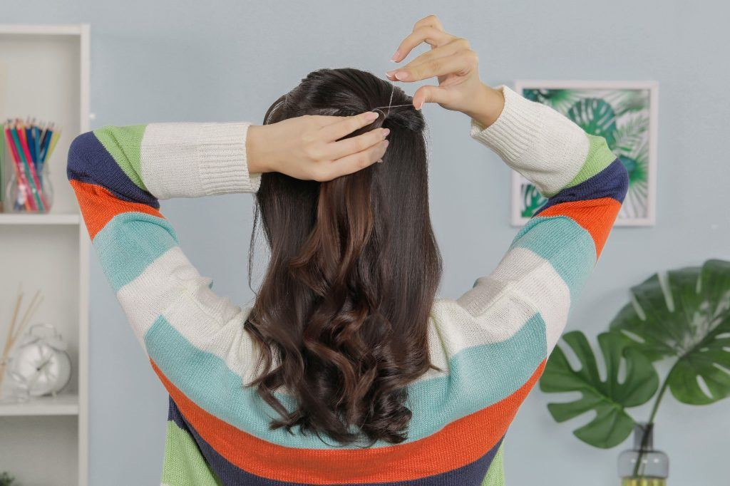 girl showing how she is tying her hair into a simple hairstyle