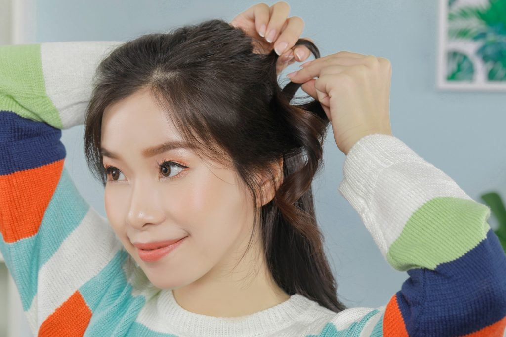 this simple hairstyle has the girl trying to make a loop out of her hair
