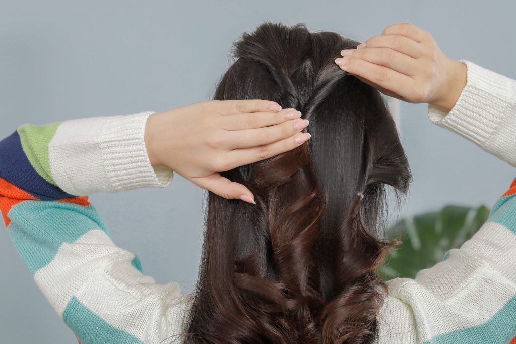 girl is facing her back to the camera and trying to loosen some strands of hair