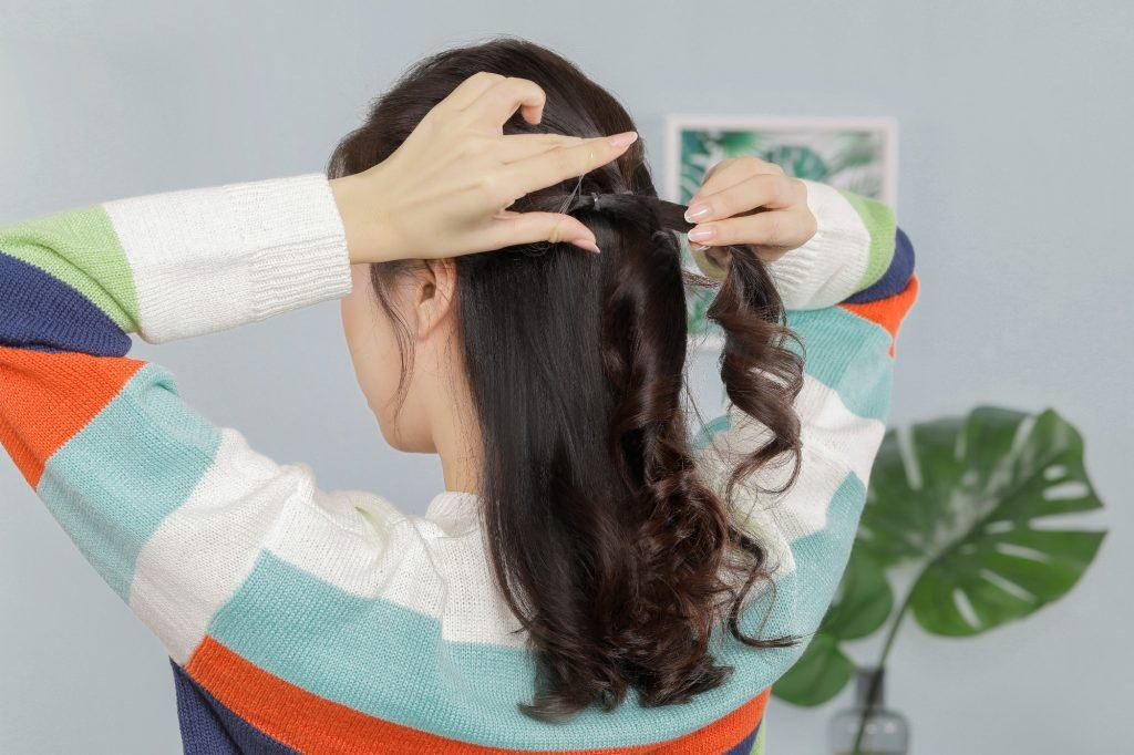 Asian girl is bringing together all three ponytails on her hair