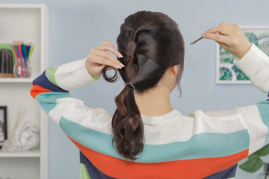 girl with her back to the camera is about to put a bobby pin into her hair