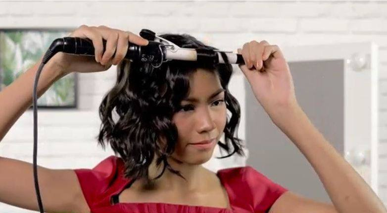 girl is curling her hair tot achieve the vintage waves for short hair