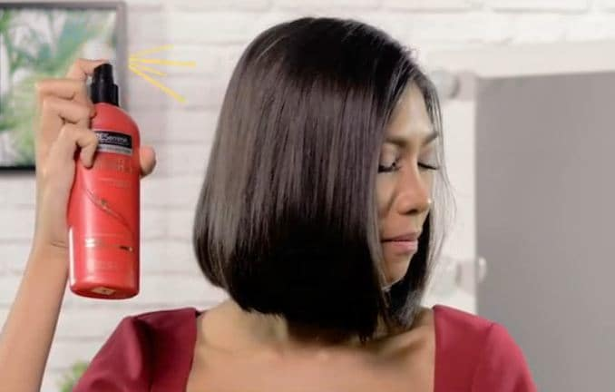 girl is spraying hairspray on her hair to prepare it for the vintage waves for short hair