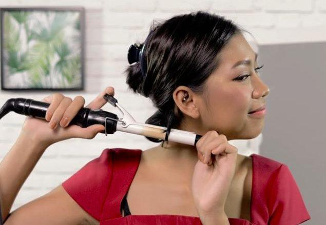 girl is curling her hair for her vintage waves for short hair