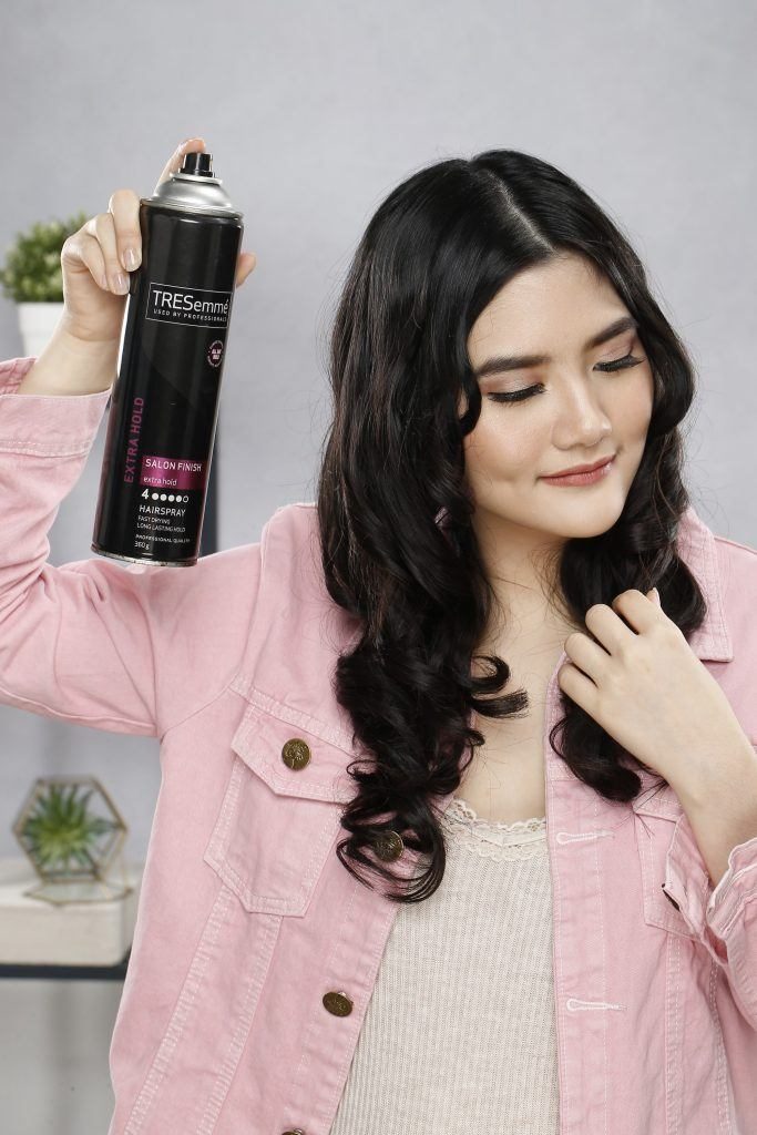how to curl hair: Girl is spraying hairspray on her hair