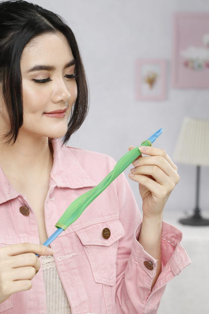 how to curl hair: Girl is holding the laverag hair roller in preparation for styling
