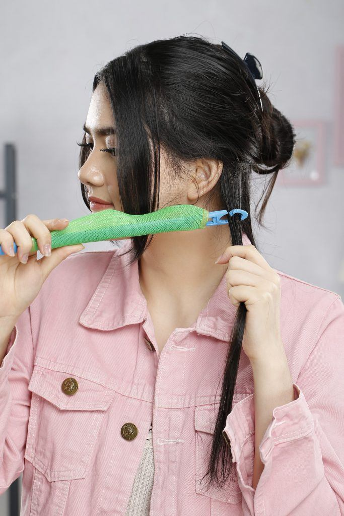 girl is showing how to curl her hair with a hair roller
