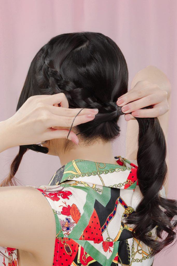 Asian girl's back is facing the camera to show her tying her hair into a ponytail as a step to making a messy bun with headband braid