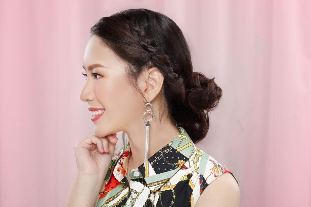 Asian girl is wearing her beautiful hairstyle with dangling earrings