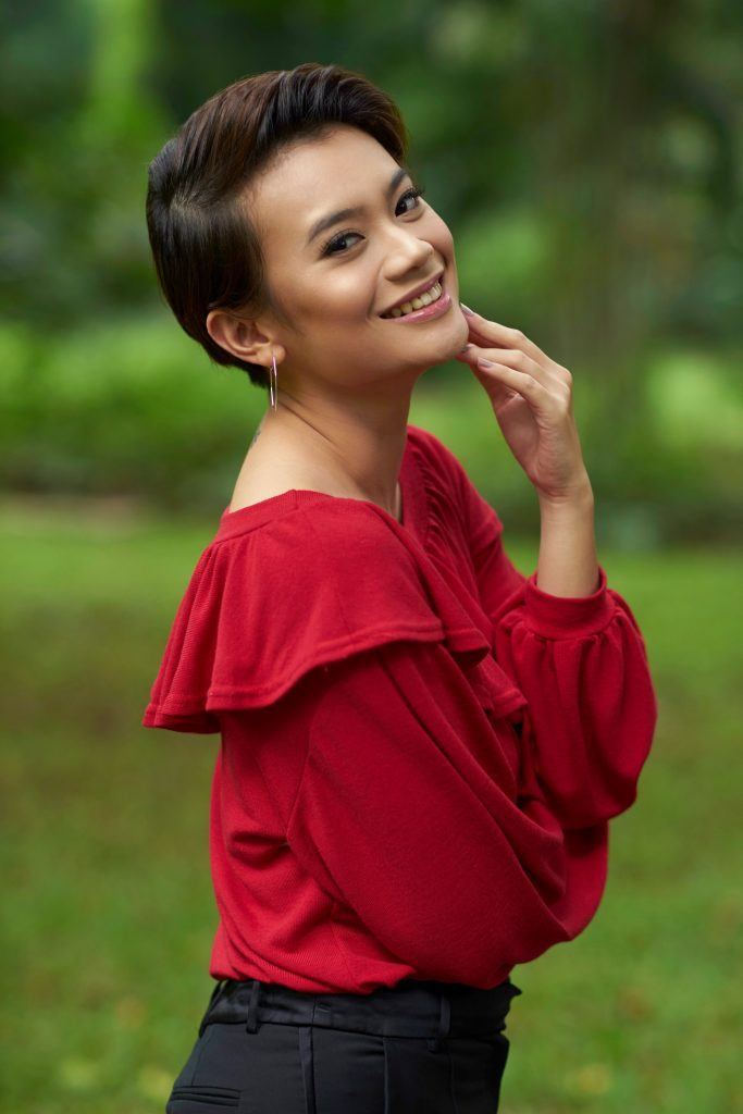 Romantic hairstyles for short hair: Asian woman with a sleek pixie cut wearing a red top