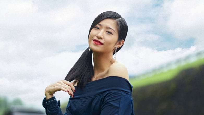 Asian woman with beautiful summer hair in a side ponytail wearing an off-shoulder top