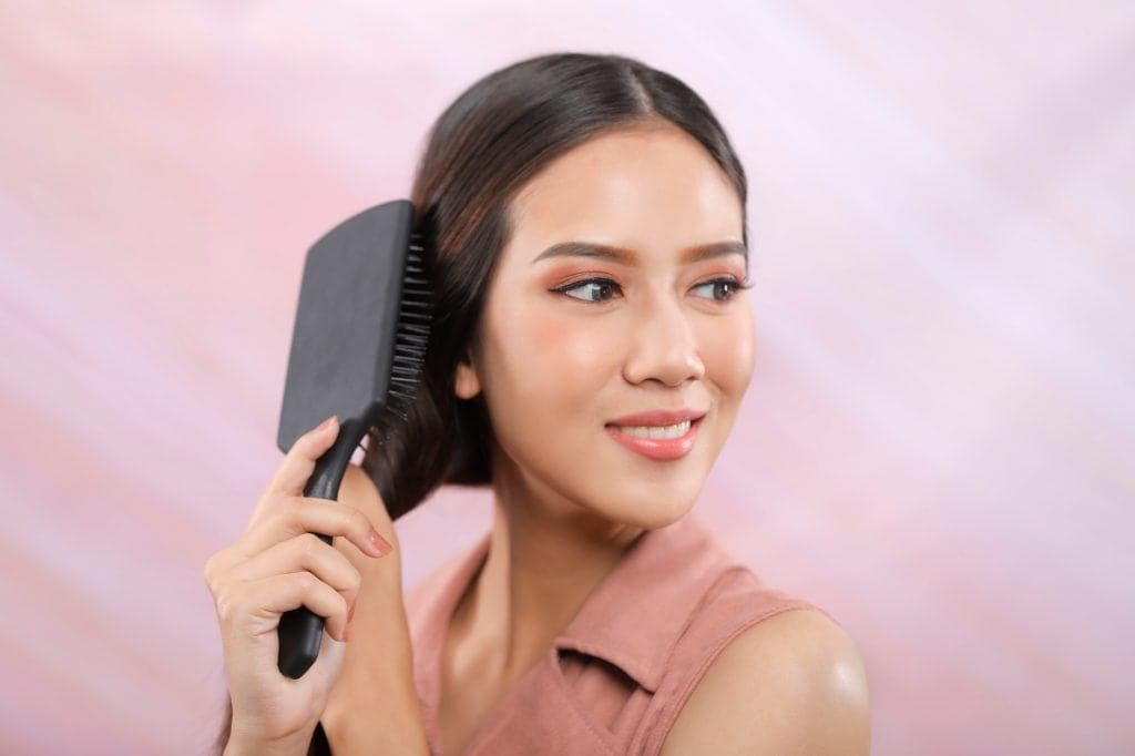 Donut bun: Asian girl is brushing her hair