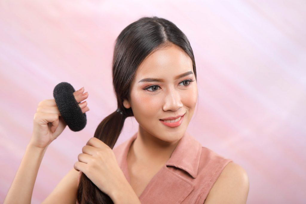 Asian girl is putting her donut bun onto her hair