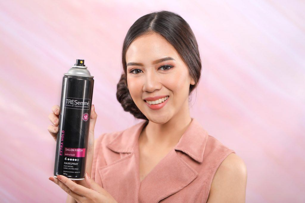 Asian girl is holding and showing her hairspray
