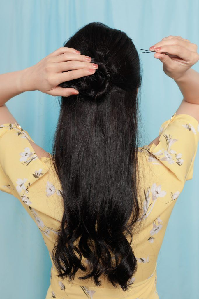 half up flower fishtail braid: girl is securing her hair with bobby pins