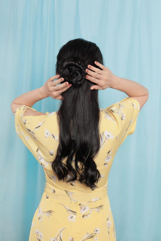 girl is trying to fix her flower bun