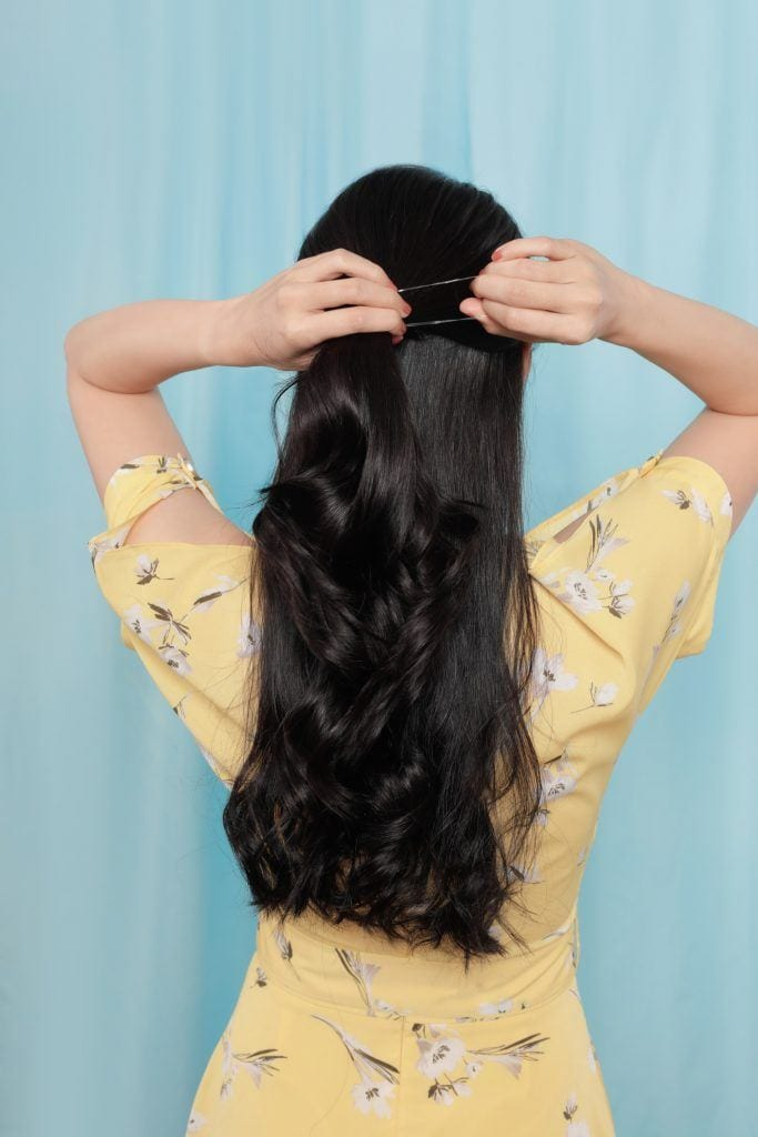 Girl's back is shown as she ties her hair into a half ponytail
