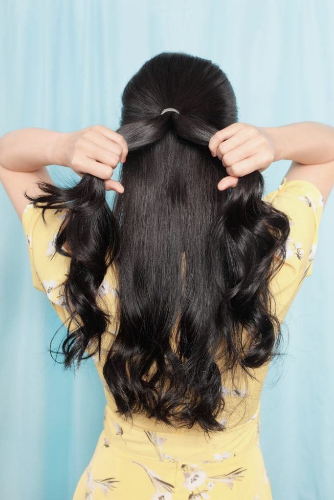half up flower fishtail braid: Girl's back is shown as she splits her ponytail into two sections